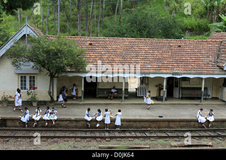 Schoolchildren in uniform at Demodara train station near Ella in the Sri Lanka highlands. - Stock Photo