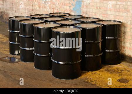 Twelve black oil drums - Stock Photo