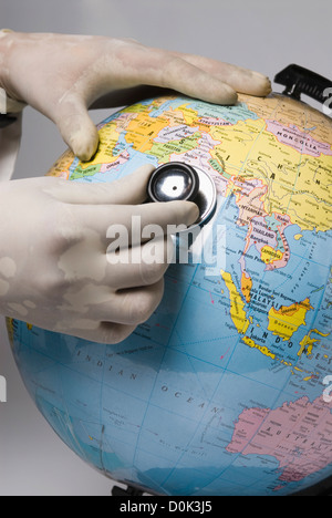 Close-up of a doctor's hand examining a globe with a stethoscope - Stock Photo
