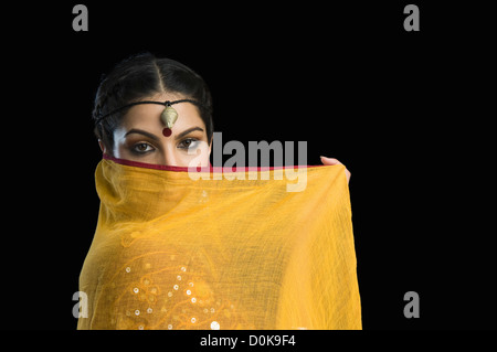 Close-up of a woman covering her face with chunni - Stock Photo
