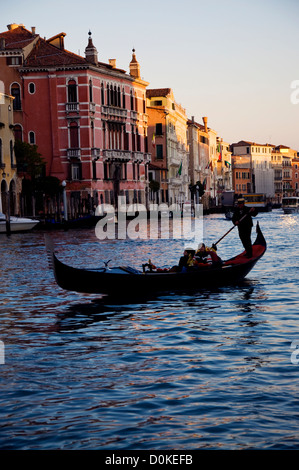 Evening sunlight catches rooftops and gondola on Grand Canal in venice Italy - Stock Photo