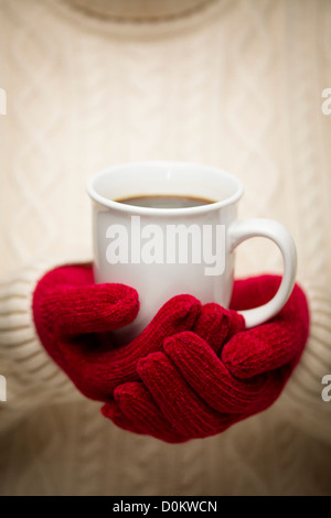 Woman in Sweater with Seasonal Red Mittens Holding a Warm Cup of Coffee. - Stock Photo