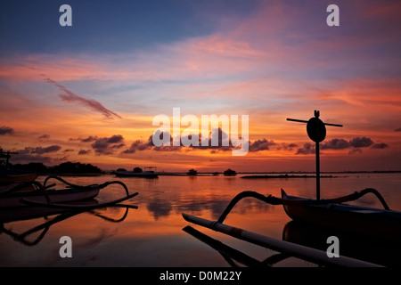 sunset over traditional fishing boats on Bali, Indonesia - Stock Photo