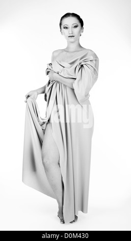 black and white photo of girl dressed and posing antique sculpture - Stock Photo