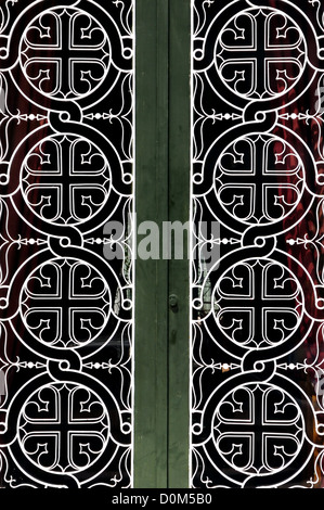 Tangled circles and cross christian religious icon pattern detail on iron church door. - Stock Photo