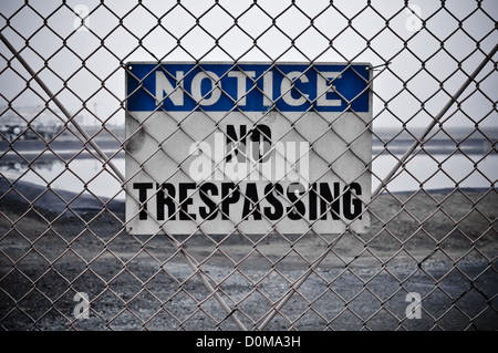 Dingy No Trespassing Sign in Front of Protected Area - Stock Photo