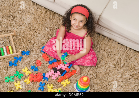 Girl playing with toys in a living room - Stock Photo