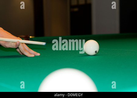 Cropped vierw image of a male hand balancing a cue and lining up with the cue ball while playing a game of snooker - Stock Photo