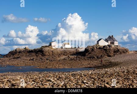 Fishermen's houses with people on skyline on Ecrehous island off Jersey, Channel islands, UK - Stock Photo