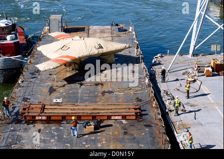 Contractors hoist the X-47B Unmanned Combat Air System (UCAS) demonstrator to the flight deck of the aircraft carrier - Stock Photo