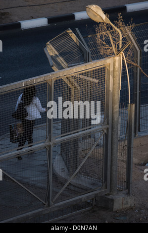 A woman carrying a shopping bag passing in front of a closed gate - Stock Photo