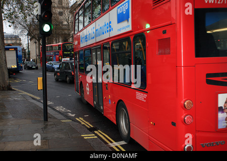 A red London double decker bus passing green traffic lights, other traffic in the background - Stock Photo