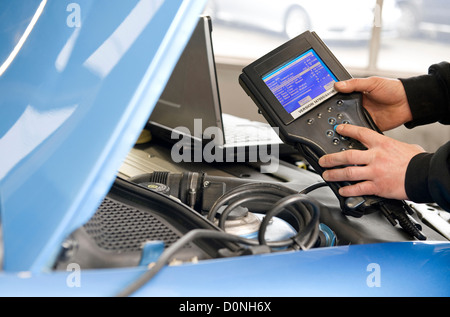 mechanic holding handheld diagnostics machine in garage workshop - Stock Photo