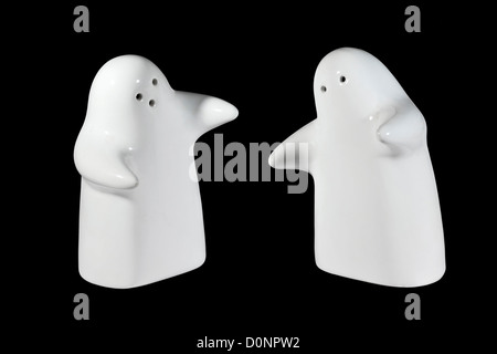 White Ceramic Hugging Salt And Pepper Pots isolated on black background that form a ying yang symbol when viewed - Stock Photo