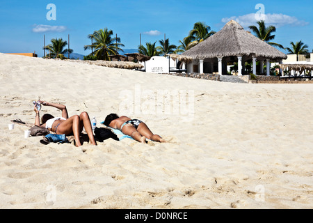two slender bronzed young women lie on white sand of playa Chahue below elegant  beach pavilion palapa  with palm - Stock Photo