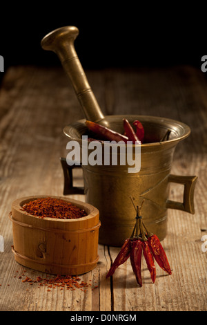 Bunch of red hot cayenne pods, bronze pounder and milled chili pepper in wooden bowl on wooden table and black background - Stock Photo