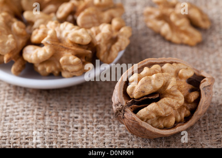 Cores of matured nuts in plate and cracked brown Circassian walnut close-up on the sackcloth background - Stock Photo