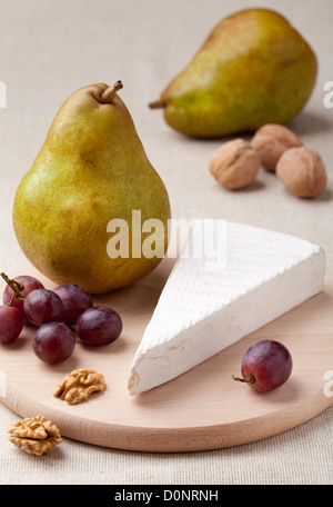 Ripe green pears, white soft cheese brie, cores of Circassian walnuts and red grapes on wooden board and linen tablecloth - Stock Photo