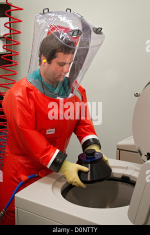While wearing his air tight safety suit in this 2007 image CDC microbiologist Dr. Scott Smith is in process placing - Stock Photo