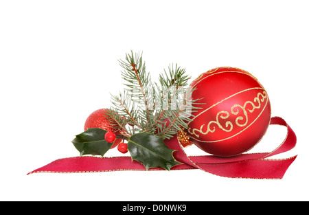 Christmas decoration, red and gold baubles with holly fir tree foliage and red ribbon isolated against white - Stock Photo