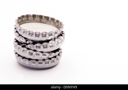 Stacked white and silver metal bottle tops - Stock Photo