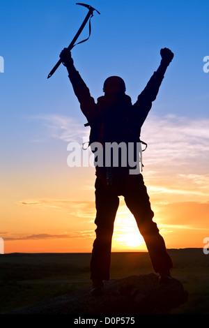Silhouette climber on mountain top - Stock Photo