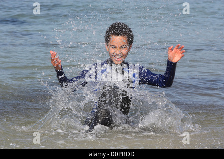 Young boy (11 years) outdoors splashing in the sea. - Stock Photo