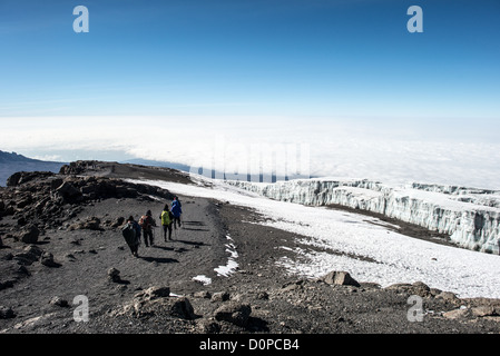 MT KILIMANJARO, Tanzania - A group of climbers begin the descent from the summit of Mt Kilimanjaro, with permanent - Stock Photo