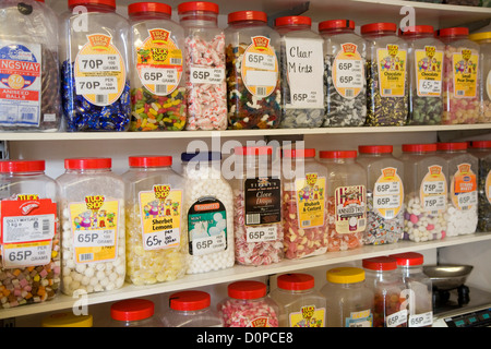Jars of sweets on shelves in sweetshop - Stock Photo
