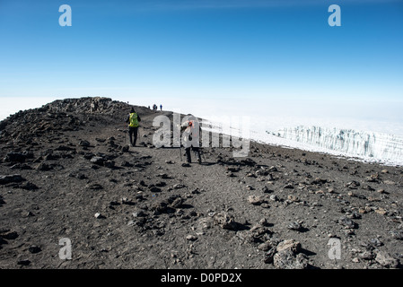MT KILIMANJARO, Tanzania - Climbers start the descent along a ridge from Uhuru Peak, the summit of Mt Kilimanjaro. - Stock Photo