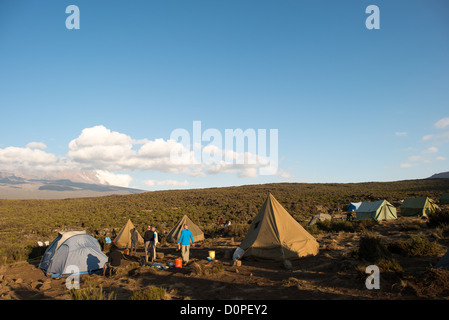 MT KILIMANJARO, Tanzania - The late afternoon sun catches the tents at Shira 1 camp on Mt Kilimanjaro. In the distance, - Stock Photo