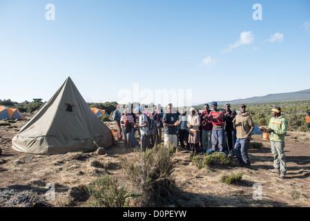 MT KILIMANJARO, Tanzania - Porters form a welcoming party for their customers at Shira 1 camp on Mt Kilimanjaro. - Stock Photo