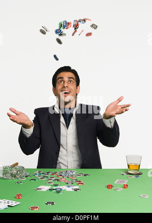 Man tossing gambling chips in a casino - Stock Photo