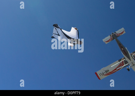 Man with wings is flying free in the sky and follows the aircraft. This wingsuit jumper is very slow falling with - Stock Photo