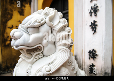 HANOI, Vietnam - Side view of an ornately carved white marble lions guard the entrance to a gate at the One Pillar - Stock Photo