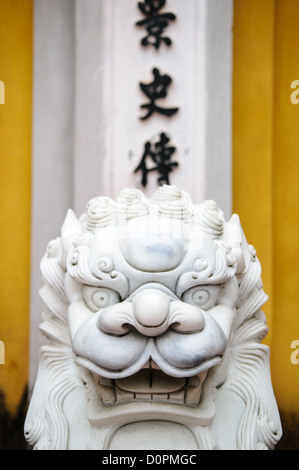 HANOI, Vietnam - Ornately carved white marble lions guard the entrance to a gate at the One Pillar Pagoda next to - Stock Photo