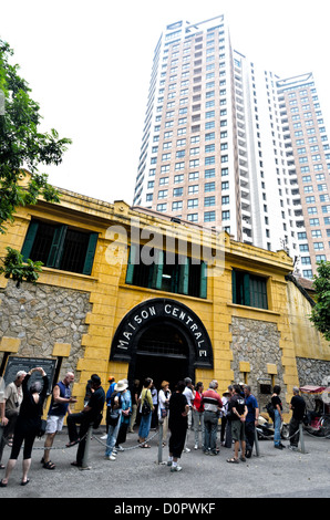 HANOI, Vietnam - In the foreground is the main entrance to Hoa Lo Prison, with tourists standing on the sidewalk. - Stock Photo