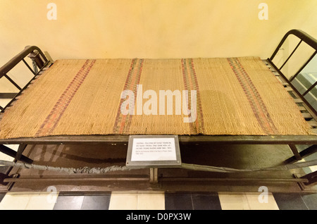 HANOI, Vietnam - A rudimentary bed on display as an example in the exhibit's case that the American pilots held - Stock Photo