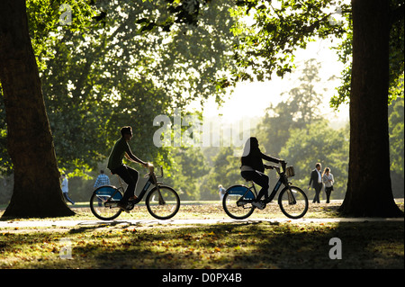 A couple cycle through Hyde Park on rented 'boris' bikes - Stock Photo