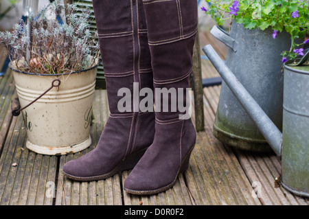 Pair of women's boots in an exterior garden setting - Stock Photo