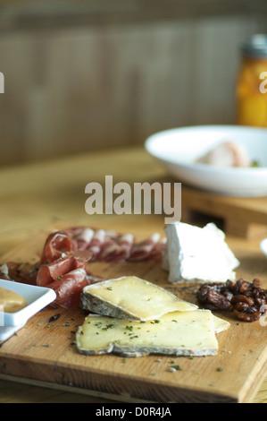 Assortment of fine cheese, blue cheese, almonds, prosciuitto, ham on a wood-grain board. - Stock Photo