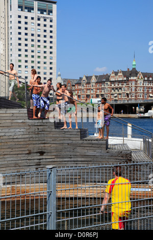Boys and girls jumping into the water from the diving tower in the Copenhagen Harbour Bath at Islands Brygge quay - Stock Photo