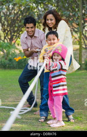 Couple with their children playing tug-of-war in a park - Stock Photo