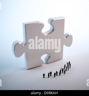 Tiny people looking at a puzzle piece - Stock Photo