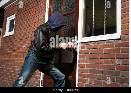 A burglar trying to get into a house by the back door - Stock Photo