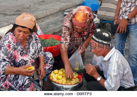 Woman selling lemons in the bazaar in Samarkand, Uzbekistan - Stock Photo