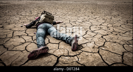 person lays on the dried ground - Stock Photo