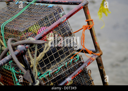 Tied onto the back of a fishing trawler are several metal crab or lobster cages - Stock Photo
