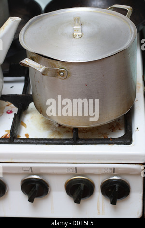 pan on old dirty gas stove - Stock Photo