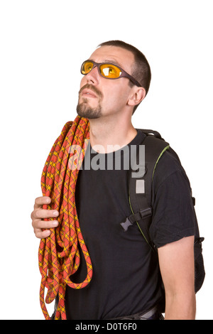 Rock-climber in sun glasses looks upwards - Stock Photo